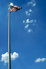 american flag blows in the wind at the top of a white flag pole