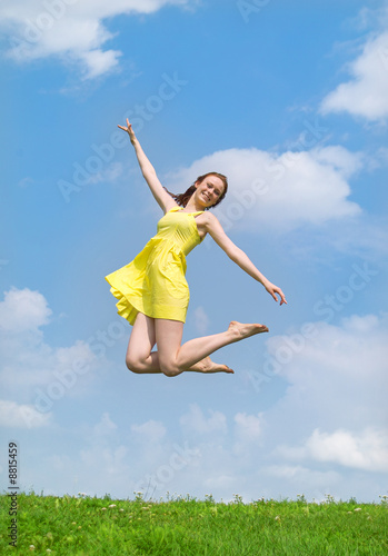 Beautiful lady in yellow dress and hat jumping