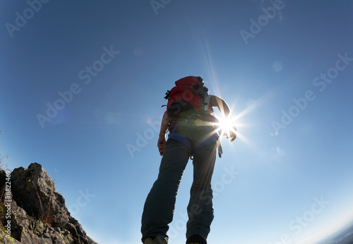 Climber standing on a stone at the top of his route