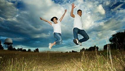 A shot of an asian couple jumping for joy
