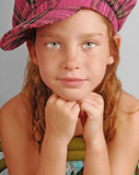Young girl in plaid hat sitting on chair poster