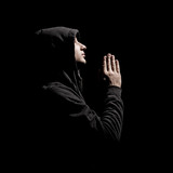 young man in black wear praying against black background