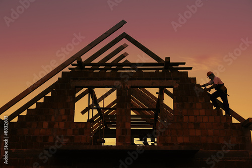 Construction worker working on house wooden roof