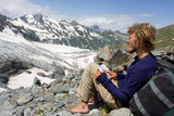 barefoot alpinist sitting on rock and looking to map poster
