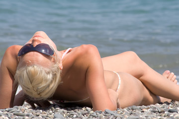 the young woman sunbathes on a stone beach