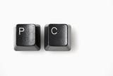 Computer keys spelling PC, shot against white poster
