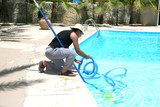 Swimming pool cleaner during his work. poster