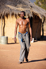 Crippled African man walking barefoot in the hot sand