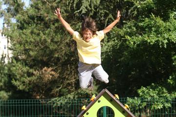 petit garçon entrain de sauter sur une aire de jeux