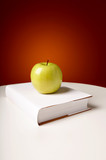 The green shining apple lays on the book poster