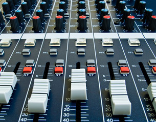 closeup of faders on audio mixer