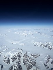 Earth view above glaciers beneath black space.