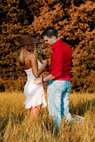 young couple in love, daytime, summer, on a field poster