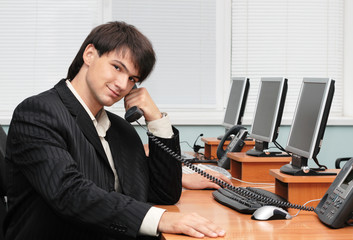 Young handsome businessman speaking by the phone