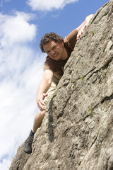 Man climbing on steep rocks, reaching for the top