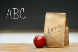 Fototapety Paper lunch bag on desk with apple