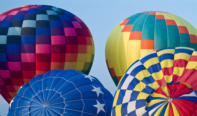 Colorful hot air balloons in various stages of inflation.