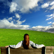 Girl relaxing in a scenic green meadow
