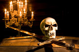 Spooky skull and sword lit by candles