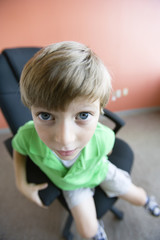 Close up of a boy sitting on a chair.
