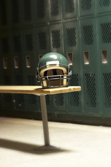 a football helmet on bench in locker room