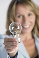 Portrait of a business woman holding a bulb.