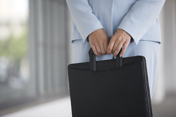 View of a business woman holding a briefcase.