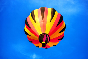 Multicoloured balloon flying in the clean blue sky.