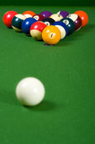 A set of billiards or pool balls on a green felt table poster