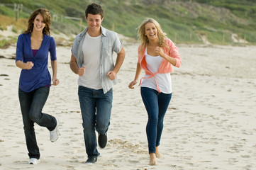 Three friends running along a sandy beach in autumn