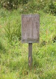 Blank wooden notice board in a meadow poster