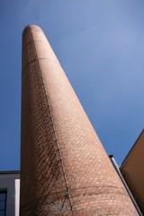 Alter, stillgelegter Fabrikschornstein ragt in den blauen Himmel