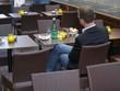 Mann sitzt alleine in strassencafe