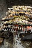 Grilled fishes laying on hot grill poster