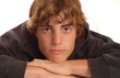 attractive young teenage boy with chin resting on hands