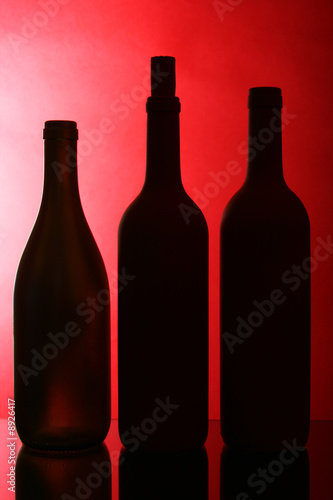 Silhouettes of three wine bottles against red background