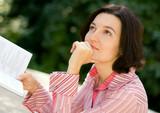 Portrait of brunet woman reading in park poster