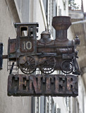 Nostalgic steam engine model against the building poster