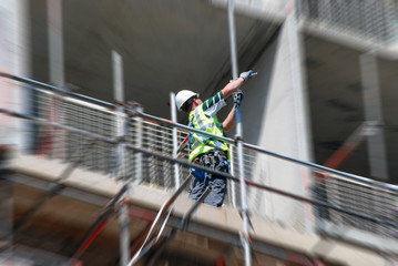 Construction worker tightens clamp of scaffolding pole