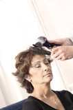 Senior woman having haircut in barber shop. poster