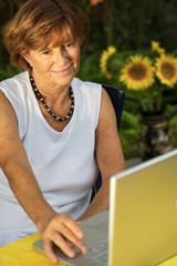 Modern senior woman using a laptop computer outdoor.