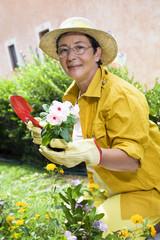 Portrait of senior Italian woman planting flowers in garden