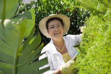 Portrait of senior Italian woman gardening, looking at camera