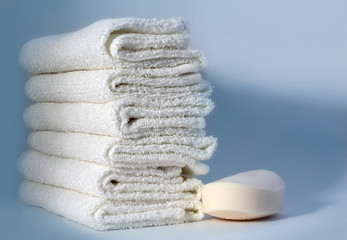 White towels and soap on a blue background