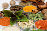 Basil leafs over assortment of various colorful spices spices - 8938493