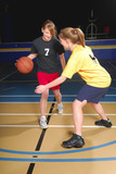 Two female basketball players compete in gym poster