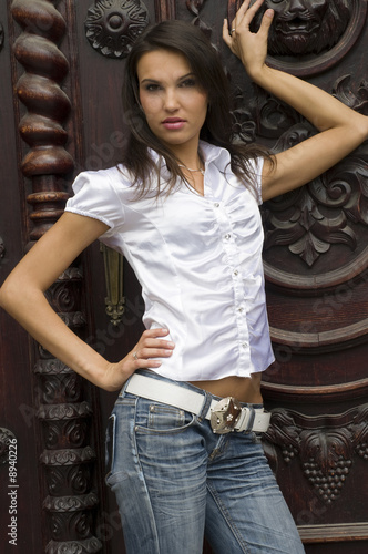 cute student girl playing as a model near an old fashion door