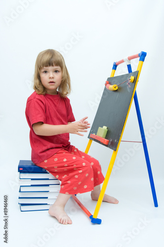 little girl sitting on a pile of books and drawing on blackboard