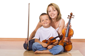 Woman and little boy sitting on the floor with violins