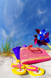 Pretty array of beach accessories on sand dune under blue sky poster
